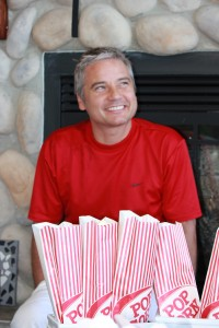 A happy guest in front of bags of popcorn