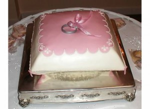 The cake to look like a ring bearers pillow with two rings
