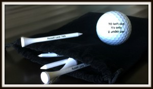 "3. Sleeve of golf balls and tees, reading ""70 isn't bad;, it's 2 under par"""